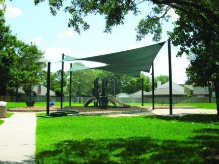green H sail shade over playground